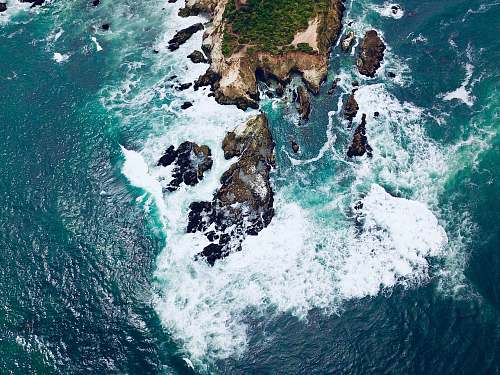 outdoors aerial photography of island surrounded with body of water ocean