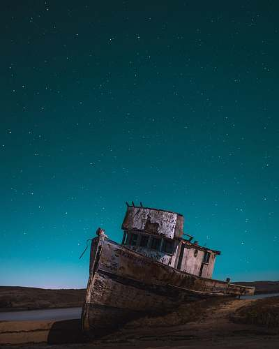 ship brown shipwrecked on shore sky