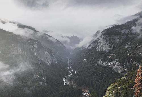 grey landscape photo of cloudy mountains slope