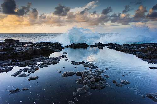 water landscape photography of rocks and barrel wave ocean