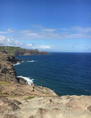land brown rock cliff beside ocean promontory