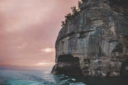 mountain gray rock formation at the sea with silhouette of trees cliff