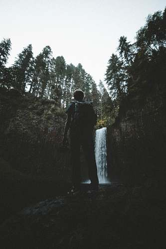 human man standing in front of waterfalls at daytime person
