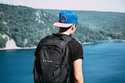person man wearing black t-shirt, black backpack, and blue fitted cap facing body of water photo human