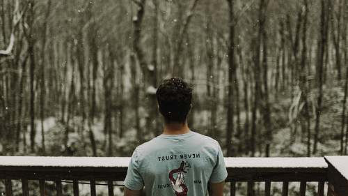 person man wearing gray T-shirt standing beside brown wooden railing during snowy day human