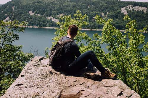 person person with backpack sitting on gray rock human