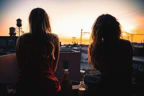 human two women sitting on rooftop while watching sunset person