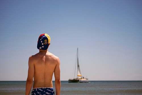 human man standing facing boat during daytime sailboat