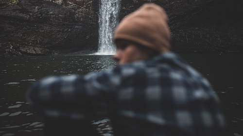 human person sitting beside waterfalls people
