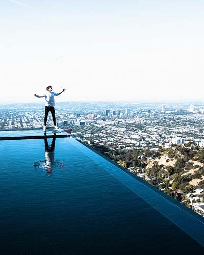 human person standing on edge of swimming on rooftop landscape