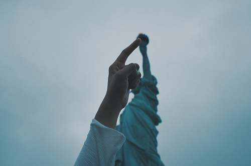 human person's pointing finger pointing statue of liberty torch people
