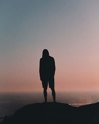 human silhouette man standing on mountain under gray sky silhouette