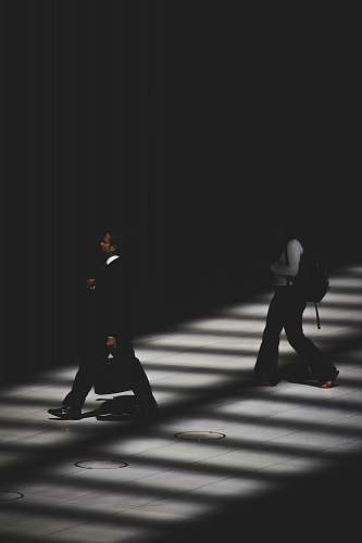 black-and-white two person walking inside building with black lighting people