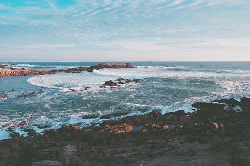 nature wavy ocean splashing on rock during daytime outdoors