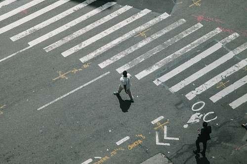 person two man walking on pedestrian lane during daytime human