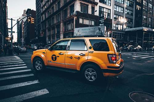 automobile selective focus photo of yellow taxi SUV parked in between road surrounded by buildings car