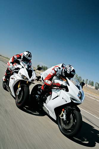 motorcycle two people riding sports bikes on gray asphalt road during daytime transportation