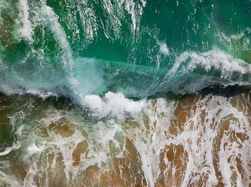ocean aerial photography of sea waves on seashore during daytime sea