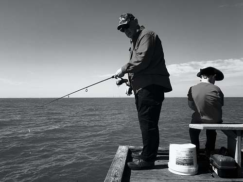 human man in black jacket and pants fishing on sea black-and-white