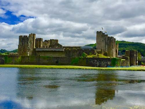building ancient castle facing body of water under cloudy sky moat