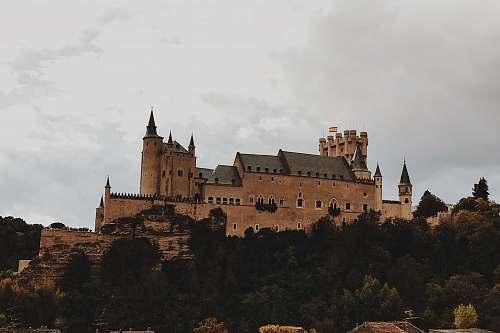building beige concrete castle on top of hill under white skies castle
