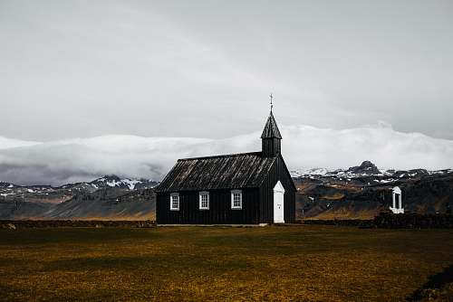 building black and white wooden house in brown field spire
