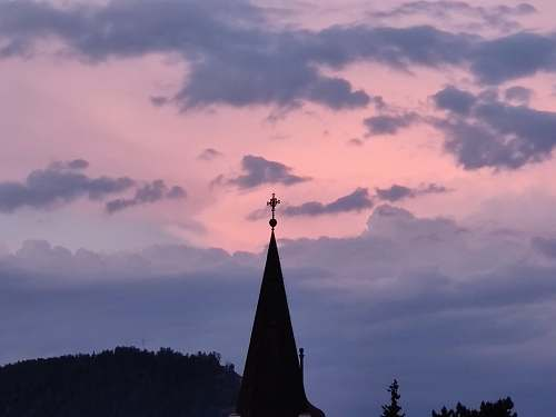 building black tower across dark clouds spire