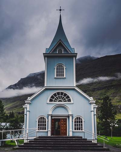 building blue and white wooden church during daytime spire