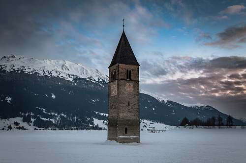 building brown and black clock tower jutting out of white snow covered field tower