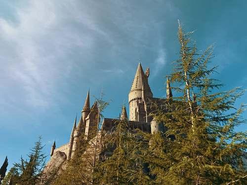 building brown castle under white clouds spire