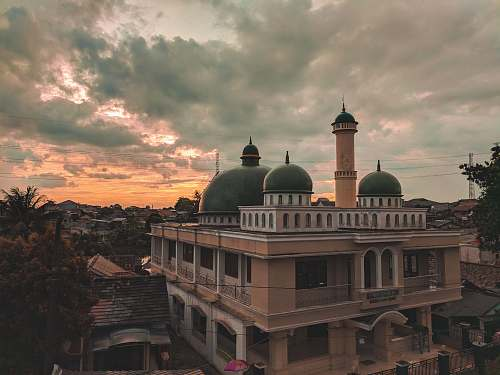 building brown concrete mosque surrounded by trees during sunset dome