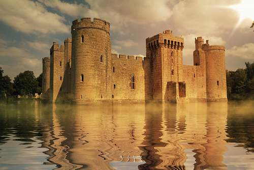 building brown concrete palace surrounded by body of water during daytime castle