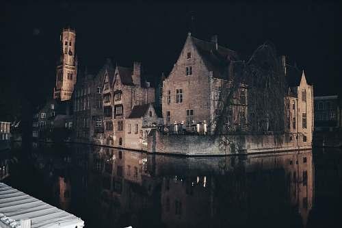 building brown house beside river castle