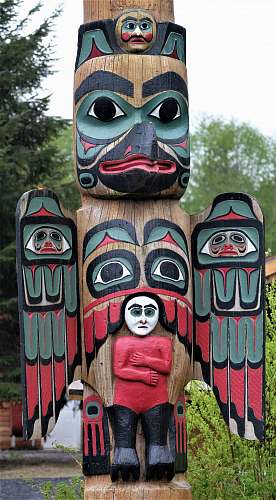building brown, red, and black totem pole near trees emblem