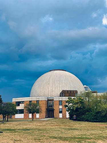 building dome building under dark clouds planetarium
