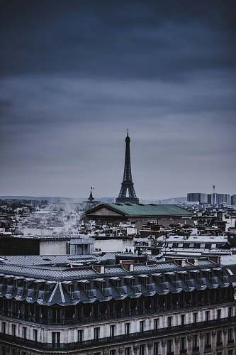 building Eiffel Tower in middle of small buildings spire