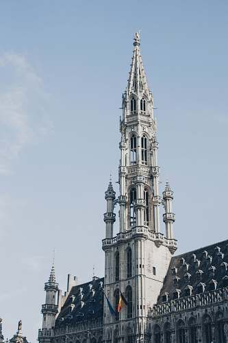 building Grand Place Market in the City of Brussels, Belgium under blue and white skies during daytime spire