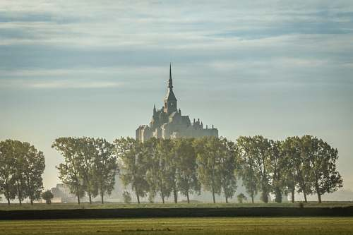 building gray castle surrounded by trees spire