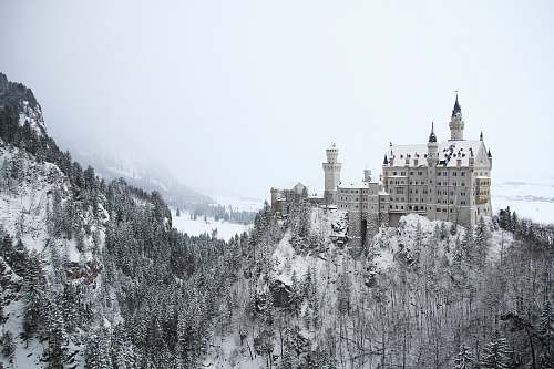 building gray concrete building on mountain covered with snow castle