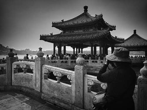 building grayscale photo of woman taking photo of temple with people black-and-white