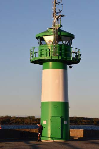 building green and white concrete lighthouse person