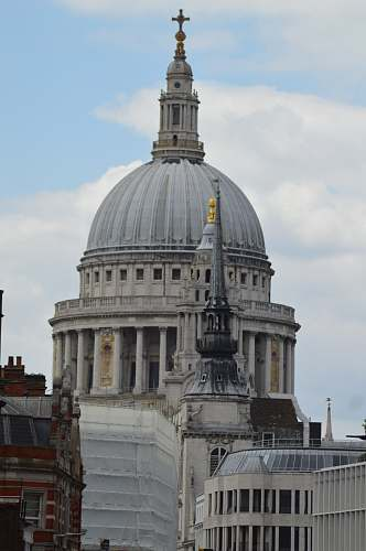 building grey cathedral under blue and white cloudy sky dome
