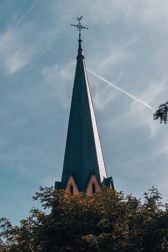 building grey church beside tree spire
