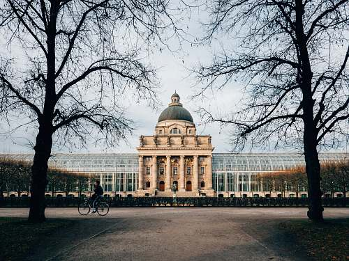 building landscape photo of person riding bicycle in front of castle bayerische staatskanzlei