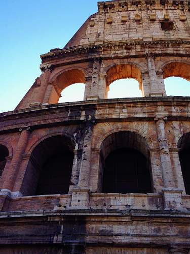 building low angle photo of brown coloseum arch