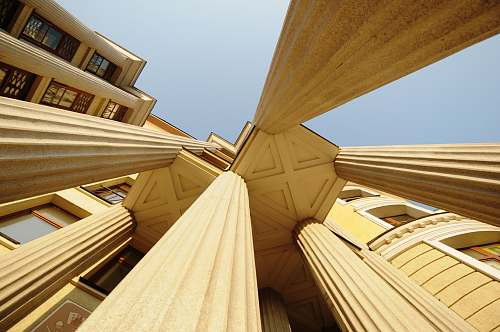 building low-angle photography of concrete pillars of a building wood