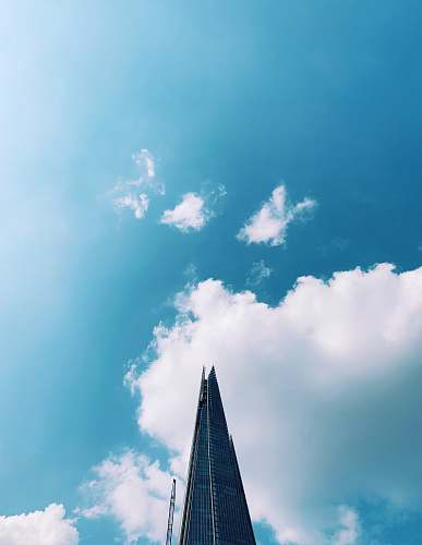 building low-angle photography of high-rise building under blue and white skies during daytime spire