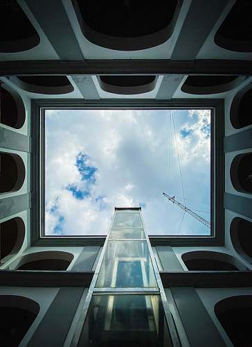 building low-angle photography of white and gray building under white and blue skies during daytime window
