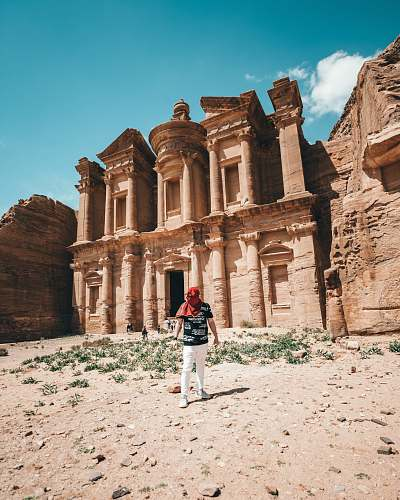building man standing beside Petra at daytime monastery