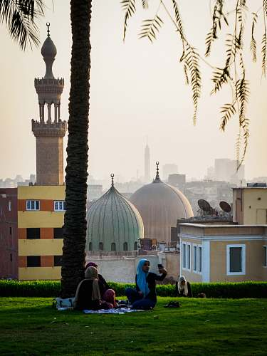 building people sitting on grass near mosque dome